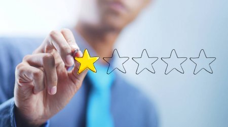 1 star review rating image. A man, blurred out in the background, is colouring in 1 star out of 5 on the screen.